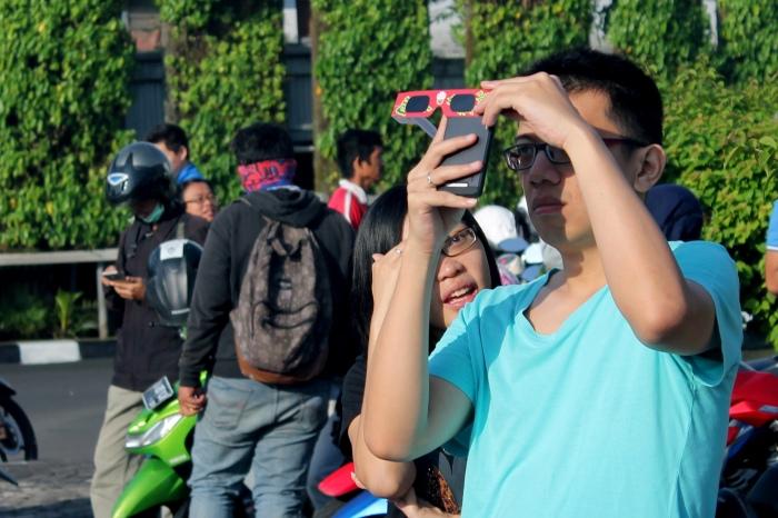 Seorang warga membidik gerhana dengan kamera ponsel dan kacamata pelindung matahari.*