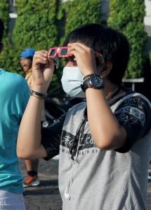 """Seorang warga """"mengintip"""" gerhana dengan kacamata pelindung matahari.*"""